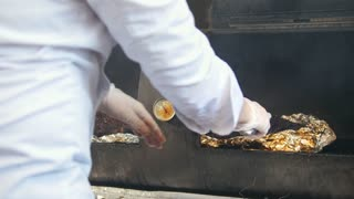 Chef smoking the meat on the grill in commercial kitchen