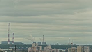 Chemical plant on city skyline - vapor and smoke from pipeline, time-lapse