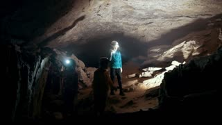 Children in helmets with lanterns comes into a dark cave