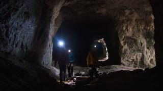 Children in helmets with lanterns explores the cave