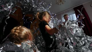 Children play carefree with shiny ribbons. A lot of fun, joy, happiness. Show animators.