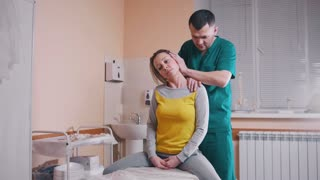 Chiropractor massaging a young woman bending and turning her neck in the medical office