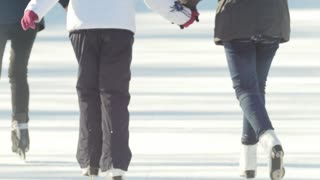 Close-up of girl's legs in figure skates skating on the ice rink