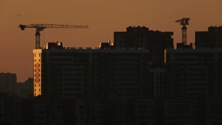 Construction cranes near residential apartments - view on sunrise