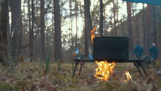 Cooking food in black iron cauldron on the campfire in forest