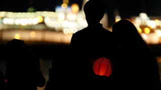 Couple in love at festival of water Lanterns on night river