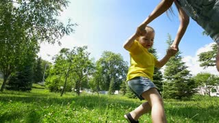 Cute little boy runs away from his happy sister through the spruce trees at sunny day