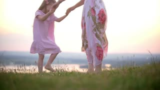 Cute little girl holding hands with mom stomps on the grass hill at sunset