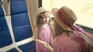 Cute little girl traveling together with her mom - holding hands and talking in train near the window