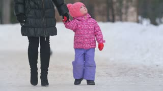 Cute little girl walking with her mother on winter street and turning her head staring at the sides