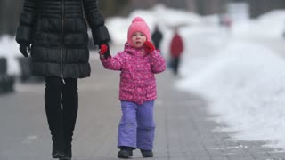 Cute little girl walking with her mother on winter street, daughter breaking out and going independently
