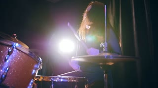 Dashing girl with flowing hair percussion drummer performing with drums, slow motion