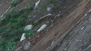 Dirt and dust crumbling off mound at industrial site - telephoto