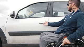 Disabled man at wheelchair gets in car