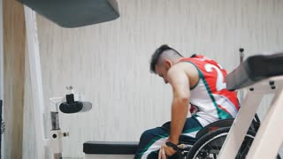 Disabled man getting up from the wheelchair doing exercise and breathing hard while training in gym