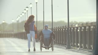 Disabled man in a wheelchair walking together her girlfriend on the quay