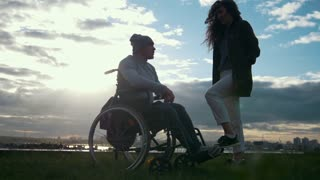 Disabled man in a wheelchair with woman talking at the cloudy sunset