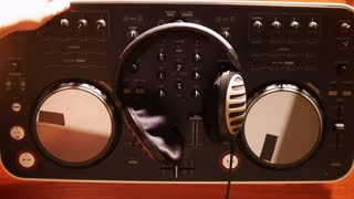 dj takes headphones from audio mixer and starts playing mausic and scratching