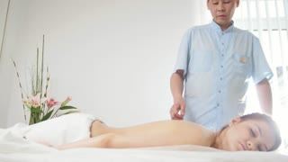 Doctor massages a woman's back in a Tibetan medicine cabinet