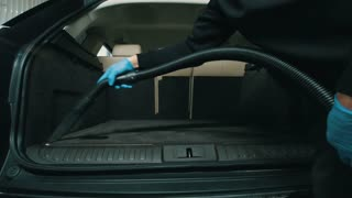 Dry cleaning of trunk, man cleans the car interior with vacuum cleaner