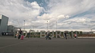 Edinburgh, United Kingdom - 12 october 2017 - People in airport of Edinburgh in front of sign - time-lapse