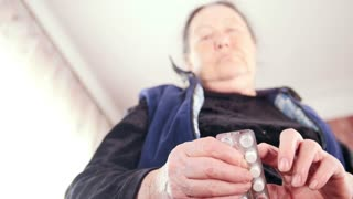 Elderly woman with pills medication packages - pension healthcare