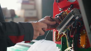 Electrician's hands installing energy system on machinery industry