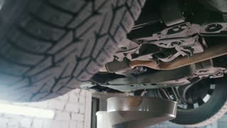 Engine oil under bottom of the car in garage workshop, close up