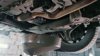 Engine oil under bottom of the car in garage workshop