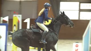 Equestrian rider on the stallion jumping throw the barrier at show jumping competition