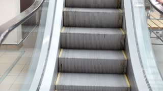 Escalator stairs in mall - moving staircase running up