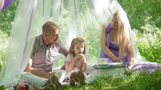Family is resting in park - father, mother and daughter have breakfast