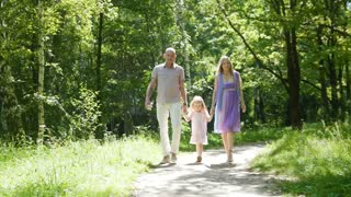Family - mammy, daddy and daughter - walking in park at summer day