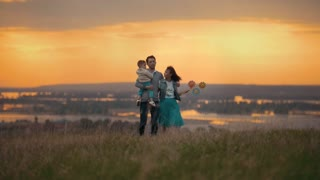 Family of 3 people walking on the field on a summer evening, mom kissing her son, orange sunset