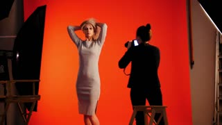 Fashion backstage: blonde girl model and photographer - photo session in studio