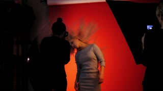 Fashion backstage: blonde girl model plays long hair - photographer take a picture in studio