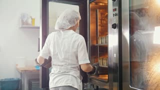 Female bakes on commercial kitchen - pulls the bread from the oven