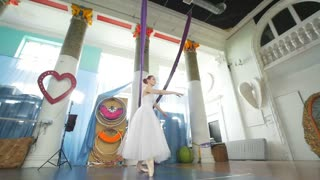 Female beautiful ballerina in white tutu performs pirouette in spacious and modern studio