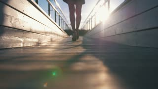 Female legs in high heels walks on footbridge at sunset