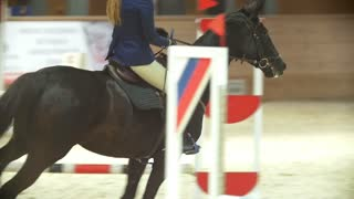 Female rider on the horse jumping over the hurdle at show jumping competition