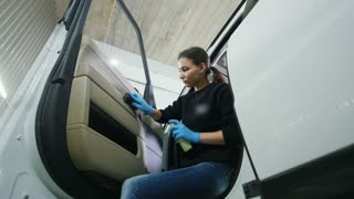 Female worker cleaning car interior with brush in the service station