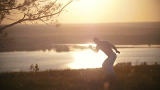 Fighter man training, orange sunset, slow-motion