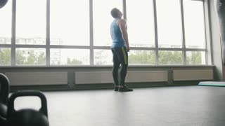 Fitness club - muscular man doing exercises warm-up near window