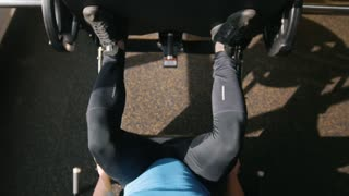 Fitness club - muscular man exercising on leg press machine - close up