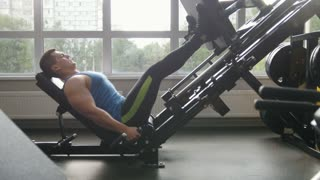 Fitness club - muscular man exercising on leg press machine - side view