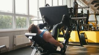 Fitness club - muscular man exercising on leg press machine
