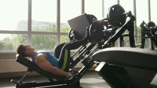 Fitness club - muscular man exercising on leg press machine