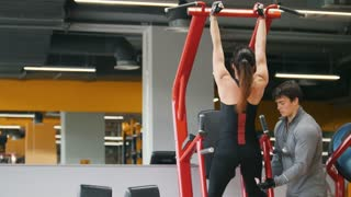 Fitness-club - young woman performs Pull-Ups with male coach - rear view