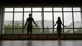 Fitness woman and muscular man jumps on rope near window, silhouette