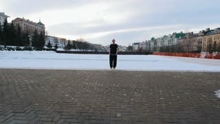 Free-running - blonde man tracer doing backflip in winter park, steadicam